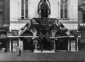 "Black and white photograph of the facade of a white building with several banners draped above the entrance. Two signs at either side of the entrance advertise ""The French Frolics."""