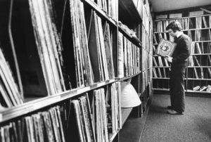 A bookcase-style shelf-lined wall takes up a majority of the frame, coming closer to the viewer. to the right, facing the wall is DJ Jon Takiff, wearing a sweater or jacket over a white collared shirt (with the collar sticking out and over top). He holds and inspects what appears to be a Looney Tunes soundtrack vinyl record sleeve. the rear wall is also lined with shelving and records.
