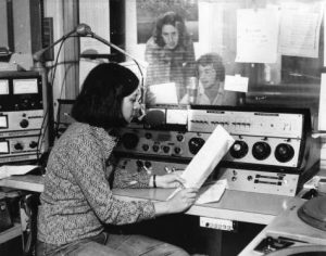 Della Lazarus sits reading a thin booklet facing right, with a microphone in front of her face and controls just behind her. A soundproof window is behind the audio controls and two men sit on the other side, one sitting (likely Bill Sinrich), reading the contents of a paper into a mic of his own.