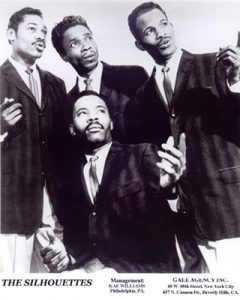 Black and white photograph of four young African American men dressing dark suit jackets, ties, and light pants. Three men are standing while one kneels in front, all are looking off to their left, at least two appear to be singing.