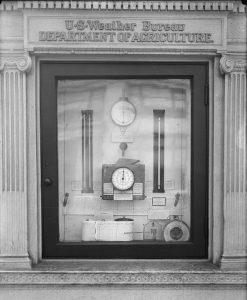 a black and white photograph of a display of weather instruments behind glass