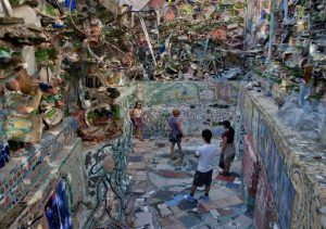 A color photograph of guests exploring the large scale mosaic Philadelphia Magic Gardens by Isaiah Zagar