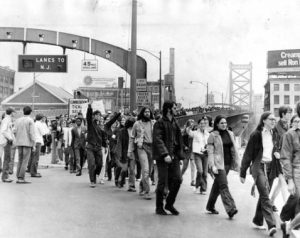 A image of protesters marching from left to right under a bridge arch which holds signal lights for lanes of traffic as well as the speed limit.  The bridge extends into the distance to the right of the frame, fading in the atmosphere.  Protesters can be seen occupying the walkway as far as can be seen.  The suspension towers of the bridge are visible, but very distant.