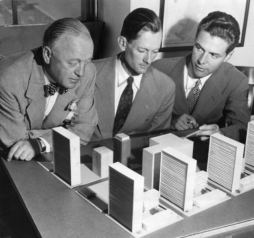 Black and white photograph of three men looking at a model of a several city blocks.