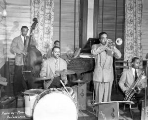 Black and white photograph of five men playing musical instruments.