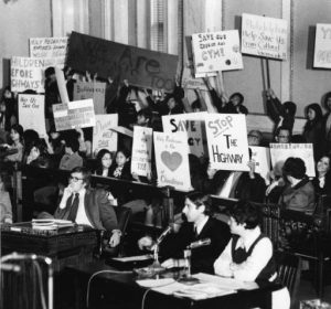 Demonstrators to save Chinatown are shown here in 1973, holding up their signs as Lynne M. Abraham from the Redevelopment Authority and James Martin of the Old Philadelphia Development Corporation testify at a hearing at City Hall in Philadelphia.