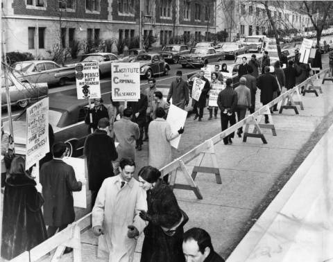 A couple walks arm in arm toward the photographer along the sidewalk at the bottom of the frame.  A line of barricades (of wooden saw-horses) stands behind them as marching protesters hold signs in the street near parked cars.  Their signs read,