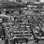 Black and white photograph depicting aerial view of a large complex of buildings.