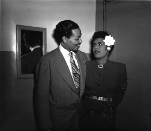 Black and white photograph of Billy Eckstine with his left arm around Billie Holliday.