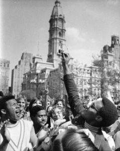 A young African American man wearing glasses, a turtleneck and jacket holds his burning draft card up above a crowd of onlookers.  The draft card is held in front of City Hall (as it is framed), making a symbolic image.  (City Hall and other buildings can be seen in the background.)  Another African American man to the left claps  with a look of satisfaction on his face as he looks upward at (likely) his friend's burning draft card.