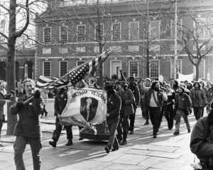A group of Vietnam Veterans marches by from  right to left, Independence Hall is behind them.  The first one carries an American flag, positioned upside-down on its pole, while two behind him carry a tattered banner that reads