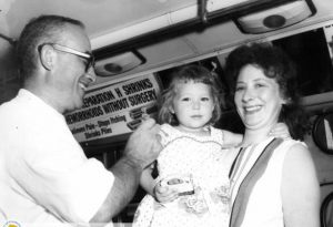 A black and white photo of a doctor administering a vaccine to a young girl being held by her mother. The vaccine is being administered on a city bus used as a mobile clinic.