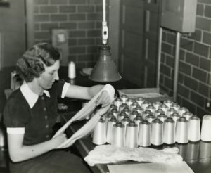 Black and white photograph of a woman inspecting nylon yarn with several spools of yarn sitting on a table in front of her.