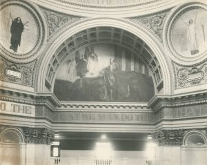 A black and white photograph of one segment of the Pennsylvania capitol building rotunda showing murals under archways