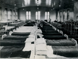 A black and white photograph of a hospital dormitory showing long rows of tightly packed beds, some with patients on them.