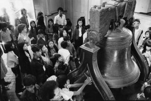 A group of Vietnamese children are gathered around the Liberty Bell while a woman speaks to them.  One reaches up to touch the bell.  They all have white tour tags hung on lanyards around their necks.