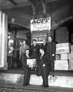"A group of well-dressed men stand in front of boxes of supplies to be donated to South Vietnam.  The boxes have a variety of markings, although most indicate canned goods such as soup (although one is marked with Schmidt's of Philadelphia Brewery).  A sign behind them indicates the Pier Office, and a sign above that reads ""ACTT: FROM THE PEOPLE OF PHILADELPHIA TO THE PEOPLE OF VIETNAM.""  A few men help load a truck just out of frame to the left."