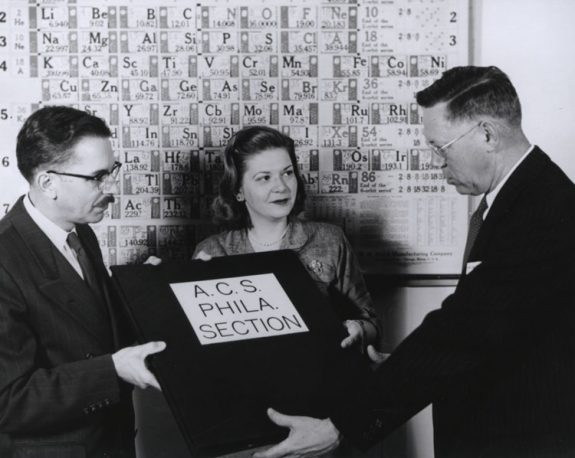 "Black and white photograph of two men and a woman. Behind the group, a periodic table hangs on the wall. The man to the left is handing over a plaque that reads ""A.C.A Phila. Section"" to the man on the right."