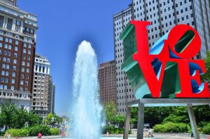 Color photograph of fountain, LOVE statue, and buildings around JFK Plaza.