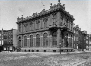 A black and white photograph of the German Society of Pennsylvania, a two-story red brick building with arched windows on the first floor, and prominent balconies and faux Greek columns on on the second floor. Decorative stone railings, urns, and cupolas adorn the roof.