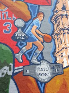 Mural painted at Spike's Trophies in Philadelphia depicting the Mighty Macs championships 1972-1974.