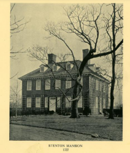 A black and white photograph of a Georgian-style mansion with a large, bare tree in front of it.