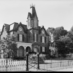A black and white photograph of a Gothic Revival style mansion with a prominent central tower