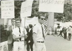 A black and white photograph of picketers whose signs read: opportunity, equality, and no society can be great without All of its citizens