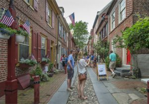 A color photograph of tourists taking a photo on Elfreth's Alley, a narrow cobblestone and brick street lined with restored eighteenth and nineteenth century row homes.