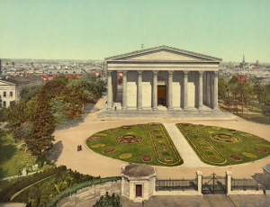 A color postcard photograph of Founders Hall, a Greek Revival-style white building with prominent front columns. It is surrounded by manicured lawns and a large stone wall.