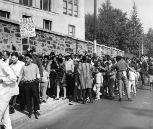 "A black and white photograph of a large crowd of African-American protesters in front of a tall stone wall at Girard College. One holds a picket sign reading ""These segregate walls must come down as the walls of Jericho"""