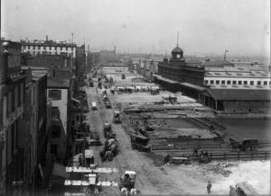 A black and white photograph of Delaware Avenue in the late 19th century showing a number of horse-drawn vehicles, a ferry depot, and industrial buildings lining the river.