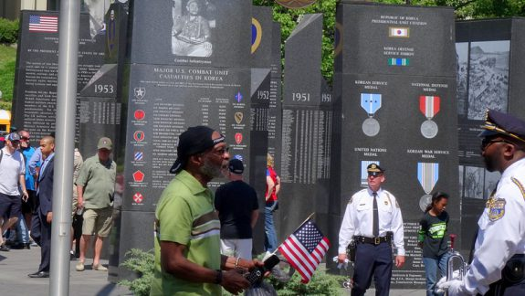 color photo of Visitors to the Korean War Memorial at Penn's Landing inspect the inscriptions on the monuments before gathering for an official tribute ceremony on Memorial Day, 2015.