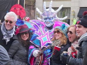 color photo of a five spectators posing with a colorful mummer during the parade in 2014.