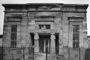 A black and white photograph of a prison building modeled after a Greek temple, in a state of severe decay after being closed for several years. A short wrought iron gate surrounds it.
