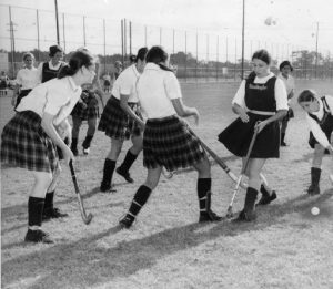 A black and white photograph of local high school girls playing field hockey.