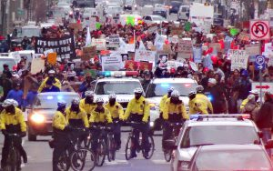 color photo of a line of bike cops in the foreground, demonstrators in the background, moving south on Broad Street on MLK Day 2015.