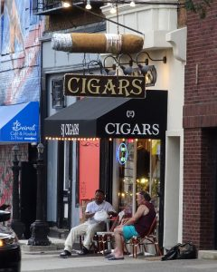 color photo of a cigar shop with two men seated outside on the sidewalk.