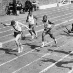Black and white photograph of high school boys runners crossing the finish line at the Penn Relays.