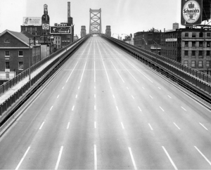 A black and white photograph of the road bed of Benjamin Franklin Bridge with no cars during an air raid drill