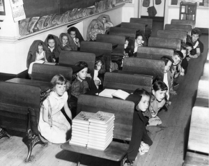 A black and white photograph showing a class room with children crouching under the desks during a