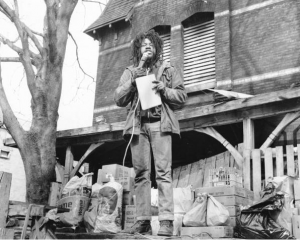 A black and white photograph of a man speaking into a microphone in front of a barricaded home