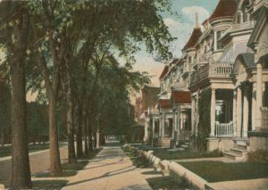 A color postcard of a row of identical victorian row homes on a tree lined street