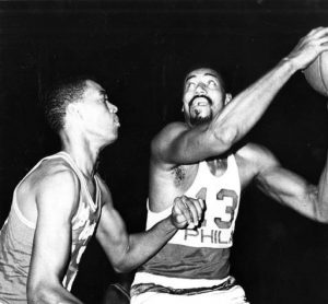 A black and white photograph of Wilt Chamberlain as a 76er playing against the Los Angeles Lakers.