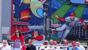 color photo with Phillies mural in background and Mural Arts Program founder Jane Golden speaking foreground.