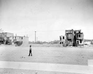 a black and white photograph of a boy walking down a mostly demolished residential street. Two clusters of derelict homes still stand.