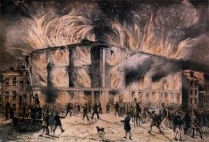 A color painting of a large building engulfed in flames with a cheering mob in the streets.
