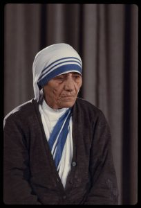 A color photograph of Mother Teresa in her characteristic blue and white habit.