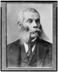 A black and white photograph of Alexander Kelly as an elder, head and shoulders, wearing a suit and tie