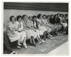 A black and white photograph of women sitting on a bench outside Apex Hosiery during a strike